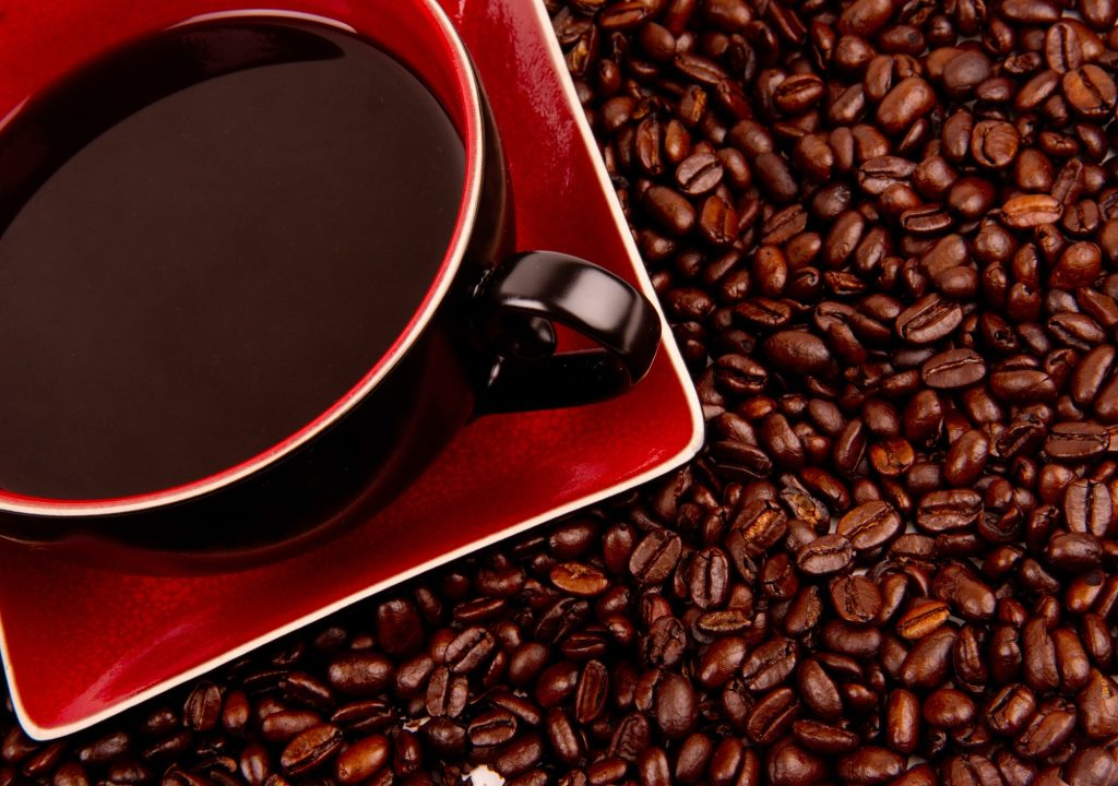 Java in Cup and Saucer Sitting in Coffee Beans